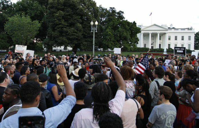 People rally near the White House during over protest about police brutality, Thursday, July 7, 2016, in Washington. (AP Photo/Paul Holston)