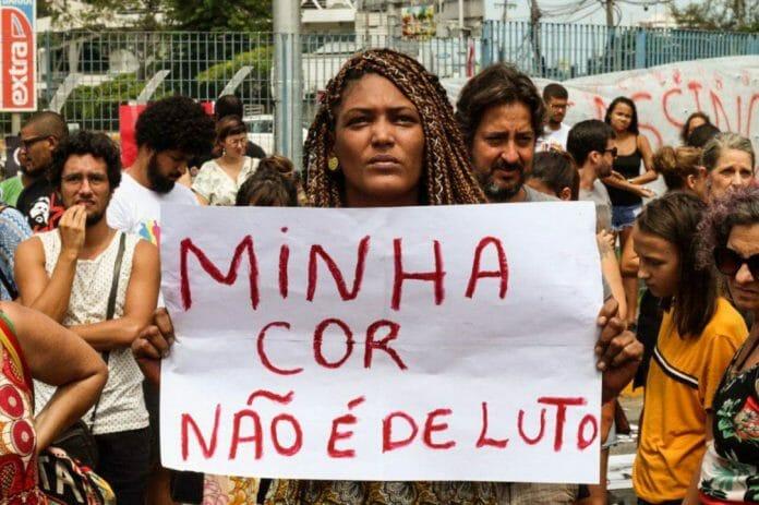 """Mulher negra segurando cartaz escrito """"minha cor não é de luto"""""""