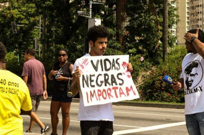"Famoso youtube Spartakus segurando cartaz escrito ""Vidas Negras Importam"""